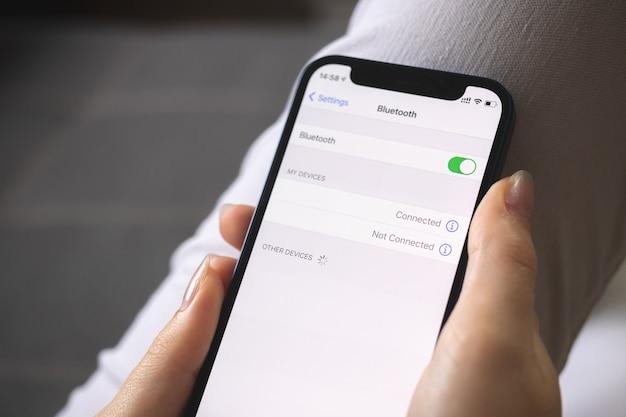 Aktivieren der bluetooth-einstellungen auf dem mobiltelefon, einstellen der bildschirm-nahaufnahme, person, die bluetooth verwendet