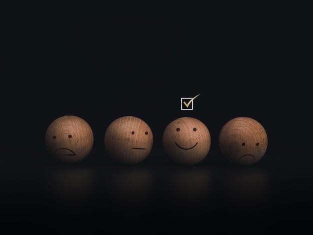 Aktivieren sie ein kontrollkästchen auf dem smiley-emoticon-gesicht auf den holzkugeln auf dunklem hintergrund. kundenservice-bewertung, bewertung, feedback und zufriedenheitsumfragekonzept.