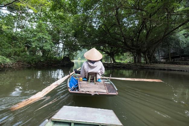 Aktivität flussabwärts auf dem boot mit vietnamesen mit fußpaddel im fluss ngo dong, ninh binh, halong bay an land