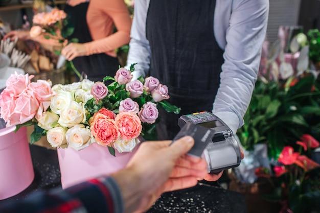 Aktuelle ansicht des mannes, der kreditkarte in der hand hält. er gibt es dem floristen. blumenverkäufer hat thereminal für karten. tisch voll von bunten blumen.