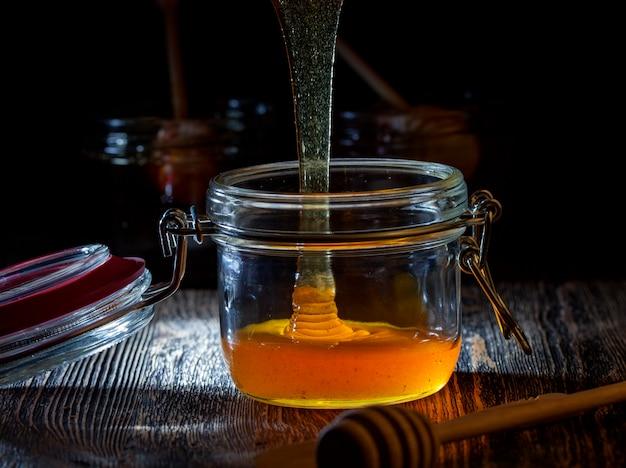 Aktueller dicker und köstlicher süßer honig, ein natürliches und gesundes lebensmittelprodukt von bienen, natürlicher bienenhonig hat eine viskose und dicke konsistenz