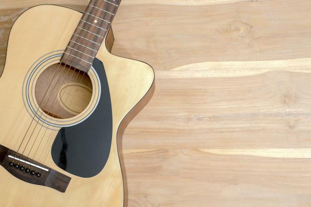 Akustikgitarre auf einem hölzernen schreibtisch.