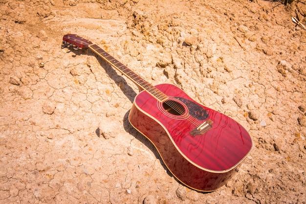 Akustikgitarre, die auf einem wüstenland liegt