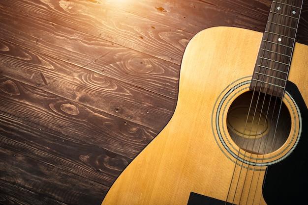Akustikgitarre, die gegen einen hölzernen hintergrund mit kopienraum stillsteht