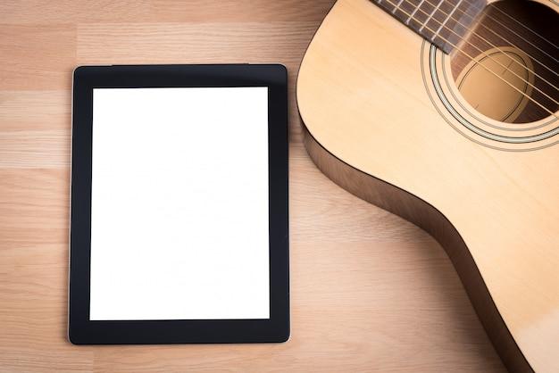 Akustikgitarre und digitales tablet auf dem schreibtisch