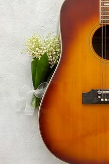 Akustikgitarre und maiglöckchen, maiglöckchen blüht auf weißem hintergrund