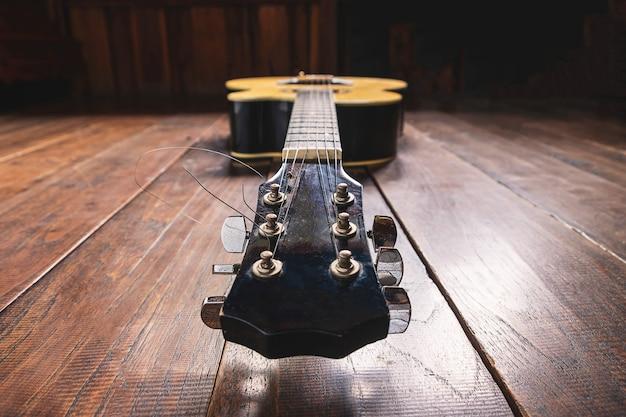 Akustikgitarreninstrument auf hölzernem hintergrund