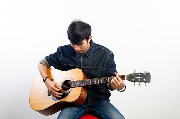 Akustikgitarrist hält die gitarre. und gitarre spielen konzepte von hobbys und entspannung in der freizeit für gute lebensqualität