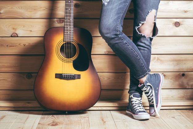 Akustische gelbbraune gitarre mit sechs saiten und weiblichen beinen in zerrissenen jeans in der nähe einer holzwand