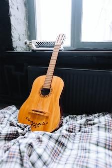 Akustische gitarre aus holz auf dem bett in der nähe des fensters.