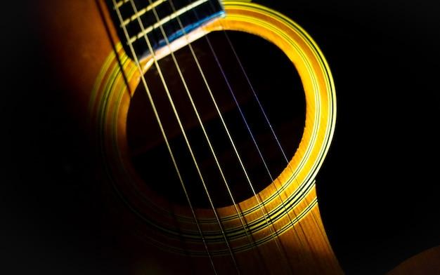 Akustische gitarre und beleuchtung auf schwarzem hintergrund