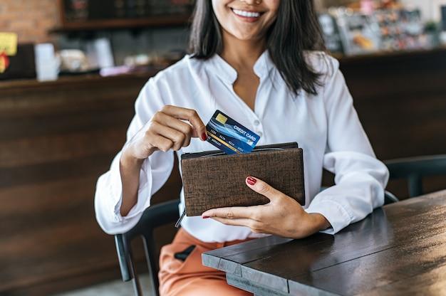 Akzeptieren von kreditkarten aus einer braunen geldbörse, um waren zu bezahlen