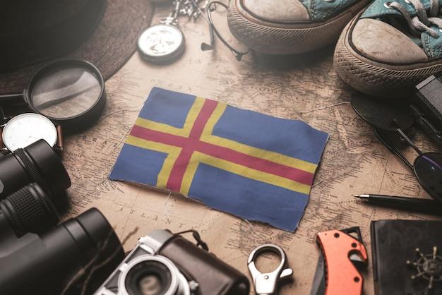 Aland islands flag zwischen dem zubehör des reisenden auf alter weinlese-karte. touristisches bestimmungsort-konzept.