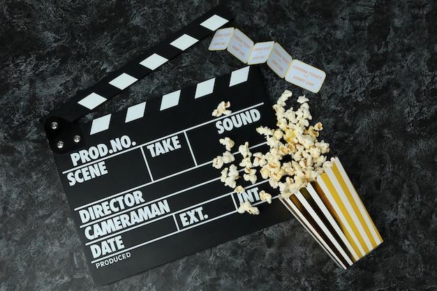 Ãlapperboard, popcorn und tickets auf schwarzem smokey hintergrund.