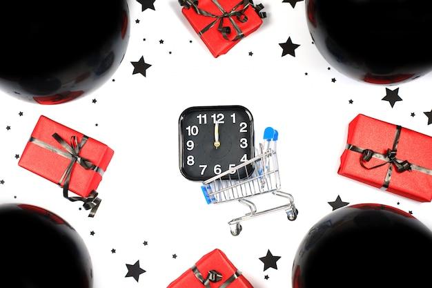 Alarm und mini-einkaufswagen mit schwarzen luftballons und geschenkboxen. einkaufs- und verkaufszusammensetzung. black friday verkauf. cyber montag.