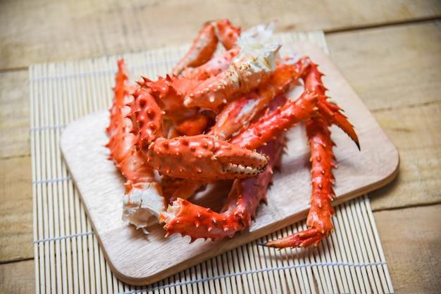 Alaskan king crab legs kochten meeresfrüchte auf rotem krabben-hokkaido des hölzernen schneidebretts