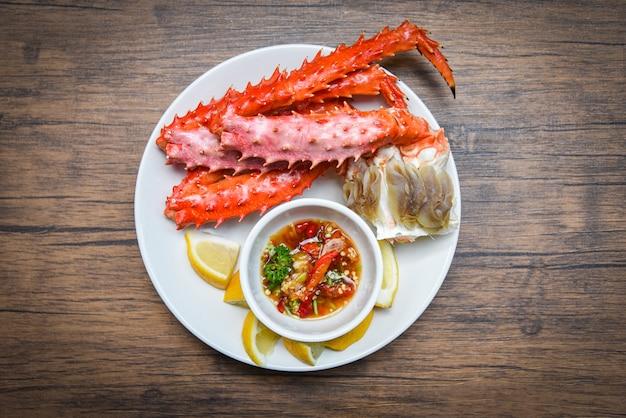 Alaskan king crab legs kochten meeresfrüchte mit zitronensoße auf weißer platte - rotes krabben-hokkaido