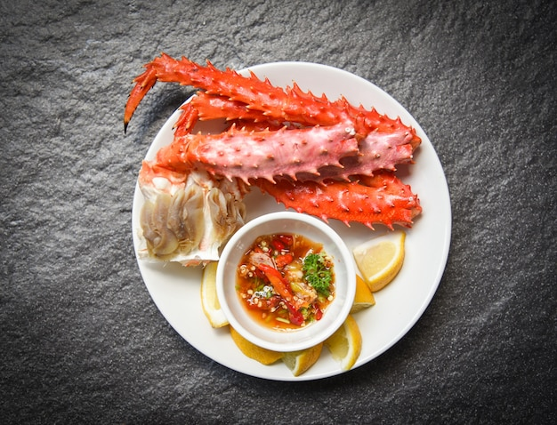 Alaskan king crab legs kochten meeresfrüchte mit zitronensoße auf weißer platte