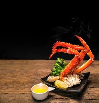 Alaskan king crab legs mit butter und zitronen auf holzplatz.