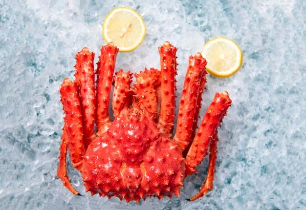 Alaskische königskrabbe auf eis mit draufsicht des zitronenhintergrundes - rote krabbe hokkaido am meeresfrüchtemarkt