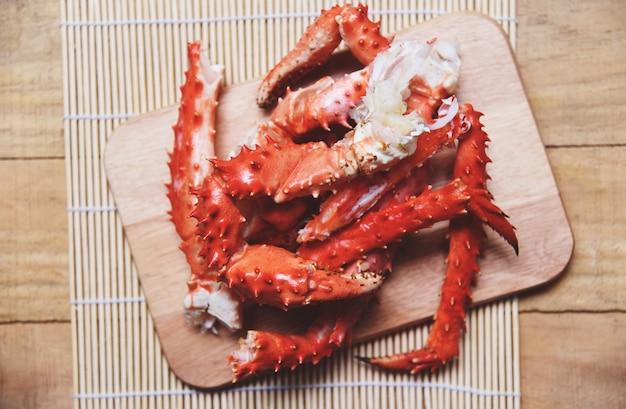 Alaskische königskrabbenbeine kochten meeresfrüchte auf hölzernem schneidebrett - rotes krabbe hokkaido