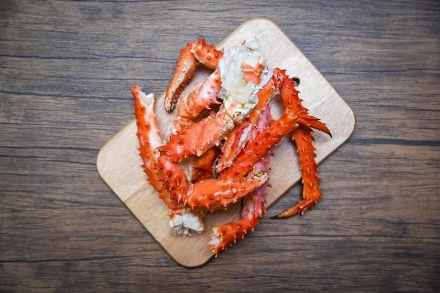 Alaskische königskrabbenbeine kochten meeresfrüchte auf hölzernem schneidebretthintergrund - rotes krabbe hokkaido