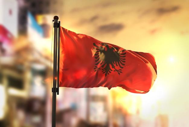 Albanien flagge gegen stadt verschwommen hintergrund bei sonnenaufgang hintergrundbeleuchtung