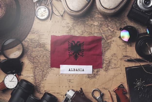 Albanien-flagge zwischen dem zubehör des reisenden auf alter weinlese-karte. obenliegender schuss