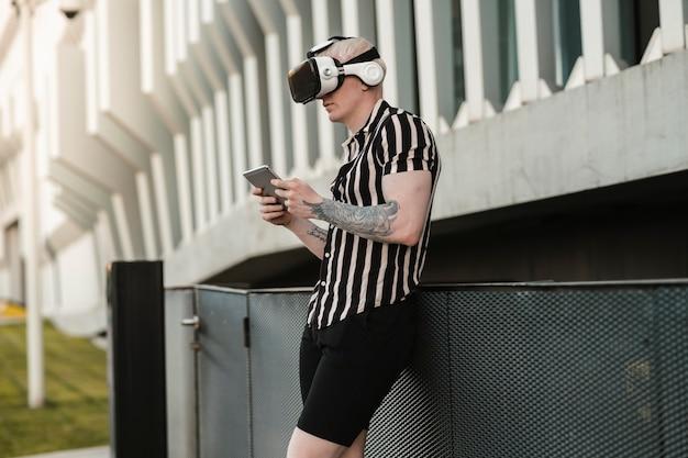 Albino blonder mann mit virtual-reality-brille, in der stadt