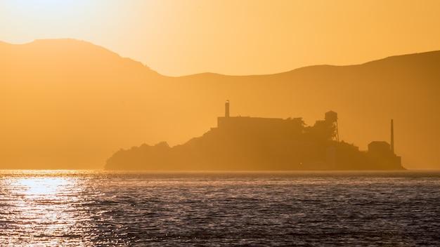 Alcatraz-inselgefängnis bei sonnenunterganghintergrundbeleuchtung in san francisco