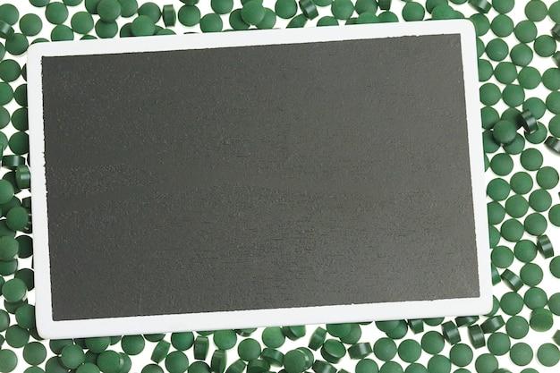 Algen spirulina hintergrund. schwarze tafel mit rechteckigem rahmen auf grünen spirulina-algentabletten.