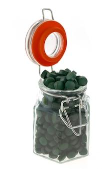 Algen-spirulina. spirulina-pillen in einem transparenten glasgefäß lokalisiert auf weißem hintergrund superlebensmittelkonzept. algen in tablettenform.