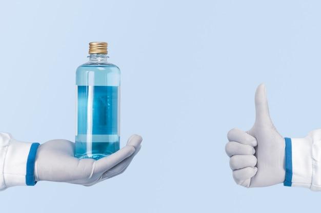 Alkohol antiseptische flasche in einer hand und zeigt daumen hoch von mitarbeitern des gesundheitswesens