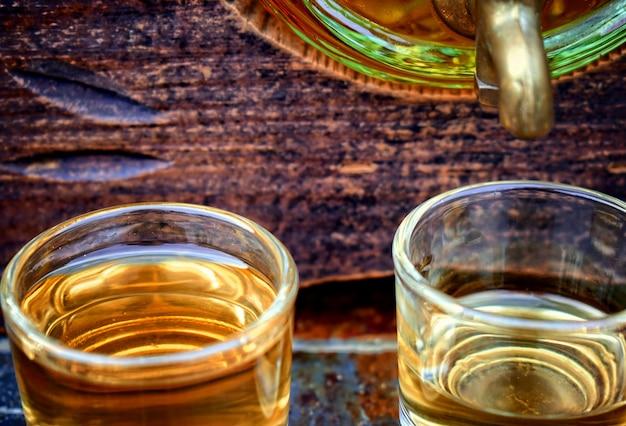 Alkohol, getränk konzept-gläser mit whiskey, alten glasfass auf stein tisch und holz zurück