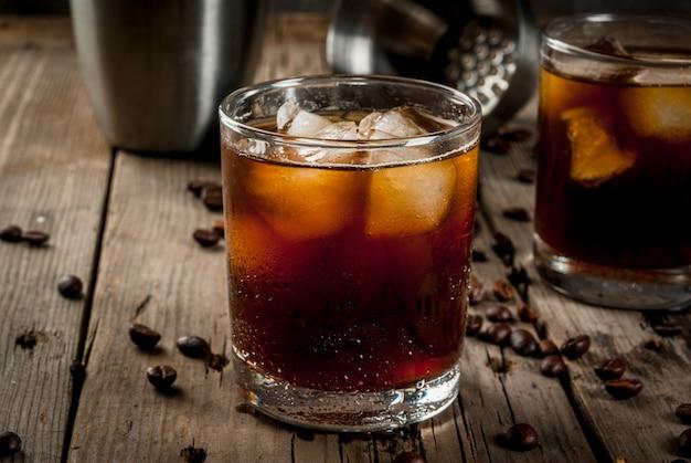 Alkohol. getränke, saftiges schwarzes russisches cocktail mit wodka und kaffeelikör auf rustikalem holztisch. copyspace