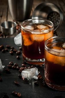Alkohol. getränke, saftiges schwarzes russisches cocktail mit wodka und kaffeelikör auf rustikalem holztisch.