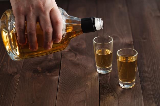 Alkohol in schnapsglas auf holztisch gießen