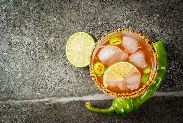 Alkohol. traditionelles mexikanisches südamerikanisches cocktail. würzige michelada mit scharfen jalapenopfeffern und limetten. auf einem dunklen steintisch. copyspace draufsicht