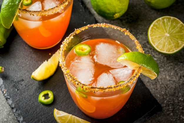 Alkohol. traditionelles mexikanisches südamerikanisches cocktail. würzige michelada mit scharfen jalapenopfeffern und limetten. auf einem dunklen steintisch. copyspace