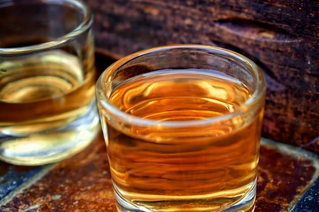 Alkohol, trinken konzeptgläser mit whisky auf steintabelle und hölzernem hintergrund.