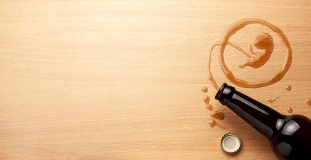 Alkohol und schwangerschaft. schlechte angewohnheiten. bierflasche und verschüttetes bier in form eines embryos