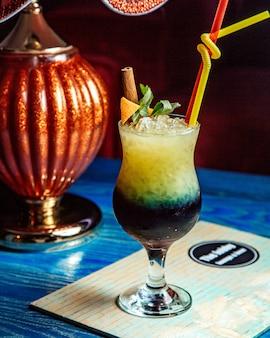 Alkoholcocktail mit orangenschalen-minz-zimtstangen-seitenansicht