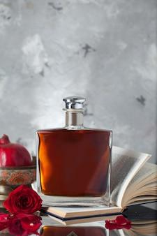 Alkoholflasche auf einem buch mit granatäpfeln und rose