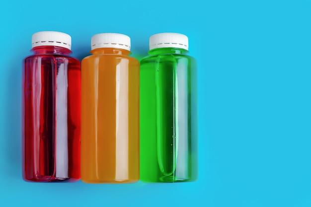 Alkoholfreie mehrfarbige kohlensäurehaltige getränke in plastikflaschen auf blauem hintergrund, das konzept der getränke auf natürlicher basis, fitness-isotonik