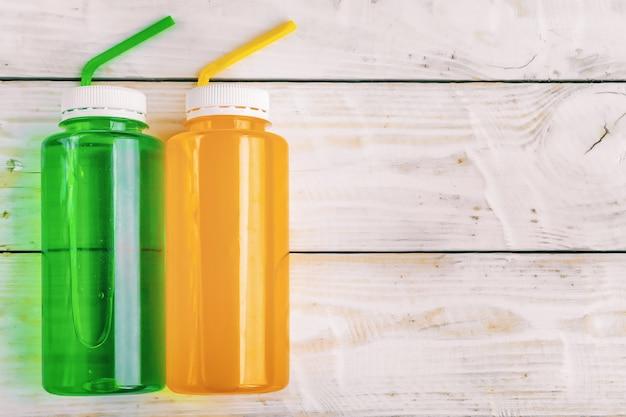 Alkoholfreie mehrfarbige kohlensäurehaltige getränke mit cocktailröhrchen in plastikflaschen auf hölzernem hintergrund, fitness-isotonik