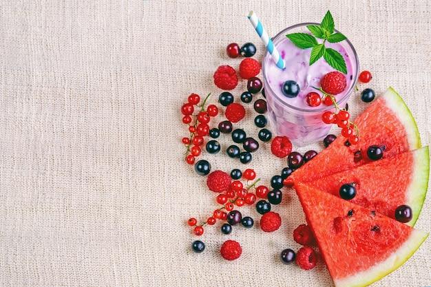 Alkoholfreie milchshake-smoothies mit frischen johannisbeeren, himbeeren, wassermelonenscheiben und minzblättern auf leinentextilien, fitnesscocktails und lebensmitteln, bio-naturprodukten