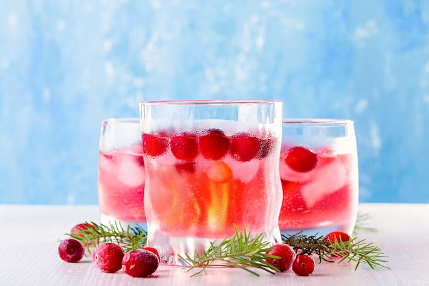 Alkoholfreier wintercocktail mit cranberry und eis auf holzuntergrund, nahaufnahme, ansicht von oben