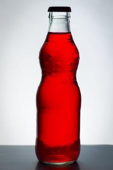 Alkoholfreies getränk, rote farbe in der glasflasche.