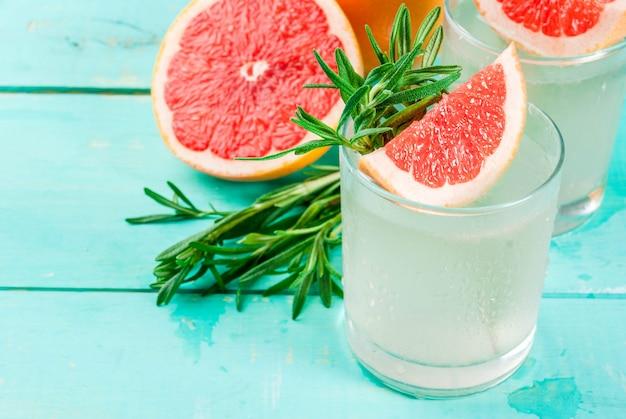 Alkoholgetränk rosemary grapefruit & gin cocktail auf hellblauem holztischhintergrund