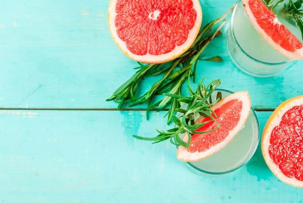 Alkoholgetränk, rosemary, pampelmuse u. gin cocktail, auf hellblauem holztisch, draufsicht